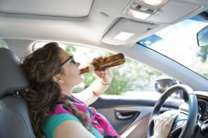 young woman drinking beer in her car